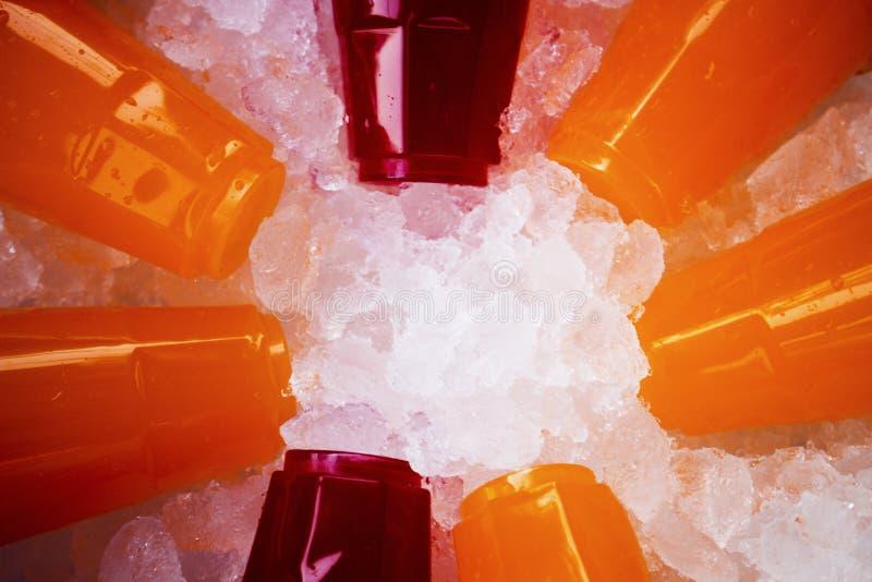 Jus d'orange et eau douce colorée sur des cristaux de glace photos libres de droits