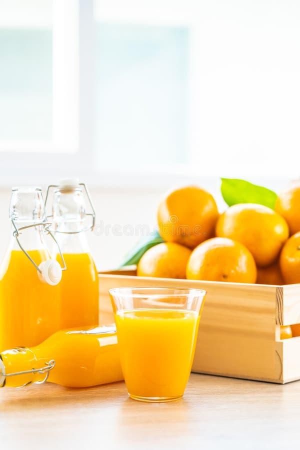 Jus d'orange frais pour la boisson en verre à bouteilles photos libres de droits