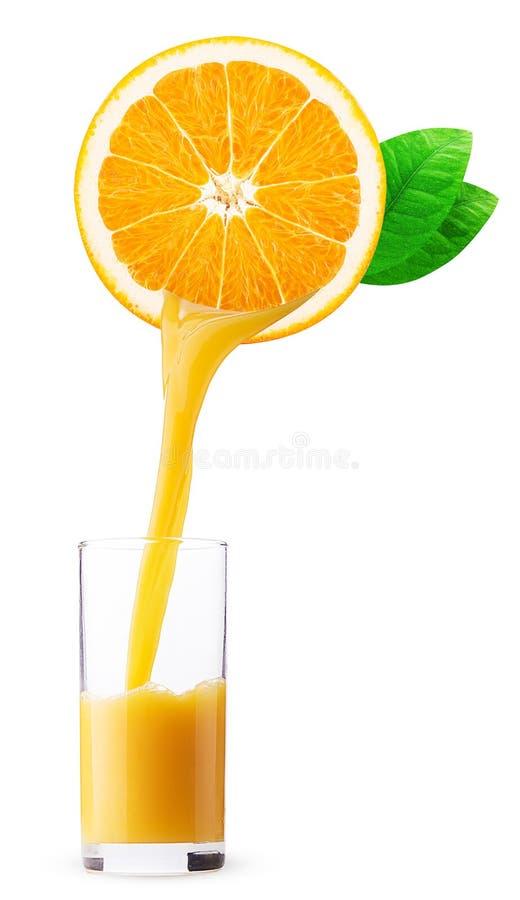 Jus d'orange frais versant dans un verre de moitié de fruit orange image stock