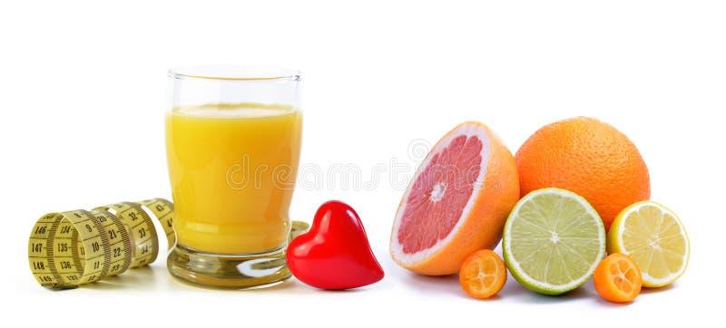 Jus d'orange in glas, meetlint, hart en citrusvruchten op een witte achtergrond wordt geïsoleerd die royalty-vrije stock fotografie