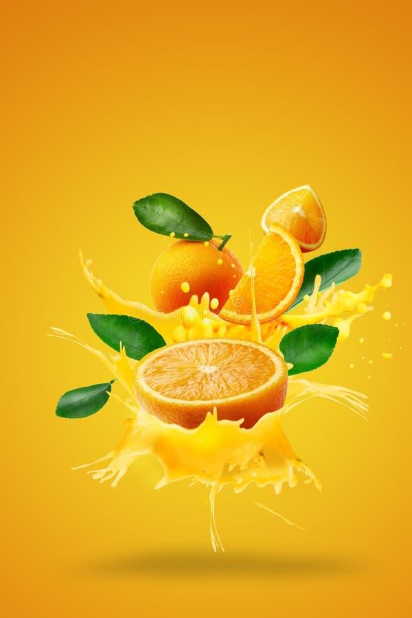 Jus d'orange het bespatten op Verse Gesneden sinaasappelen en Oranje fruit dat over Oranje achtergrond worden geïsoleerd royalty-vrije stock afbeeldingen