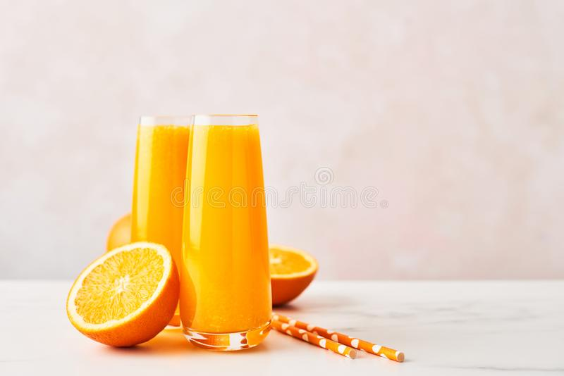 Jus d'orange in lang glas met oranje plakken en stro royalty-vrije stock foto