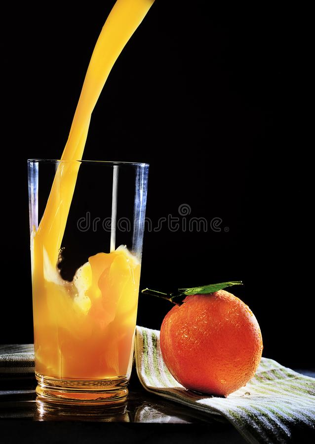 Jus d'orange pleuvant à torrents dans la glace images stock