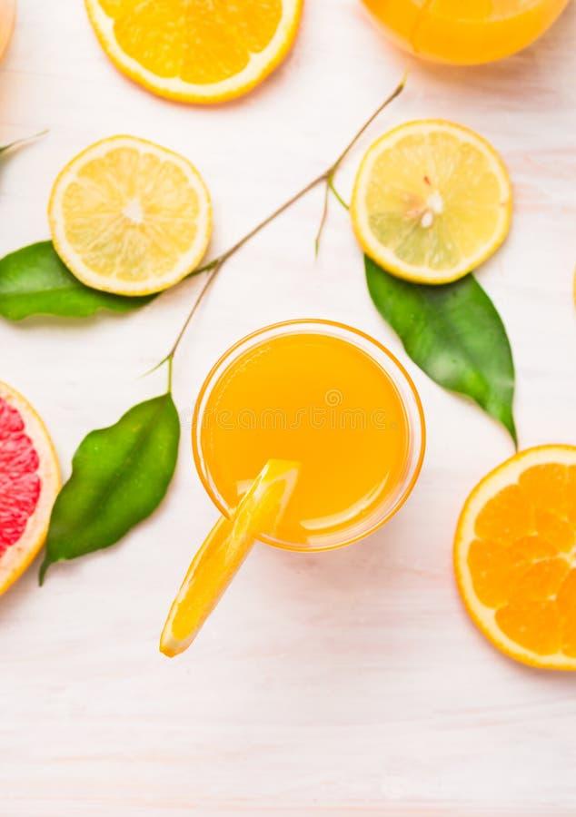 Jus d'orangeglas met plakken van citrusvrucht en groene bladeren op witte houten royalty-vrije stock afbeeldingen