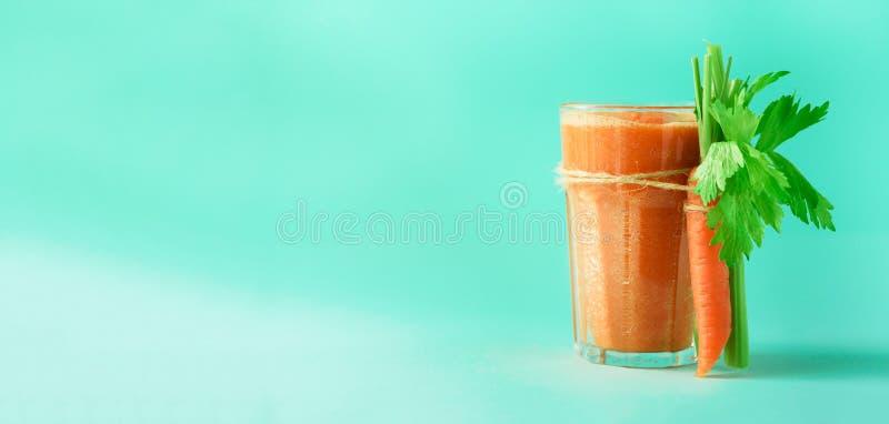 Jus de carotte organique avec des carottes, céleri sur le fond bleu Smothie de légume frais en verre drapeau Copiez l'espace photographie stock libre de droits