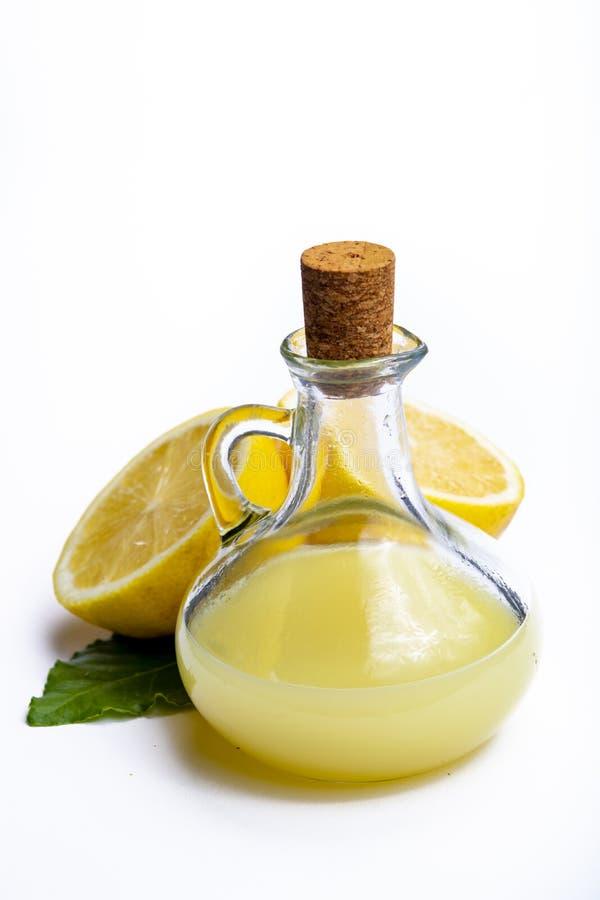Jus de citron frais fait à partir des citrons siciliens jaunes mûrs utilisés pour faire cuire dans la bouteille en verre sur le p image stock