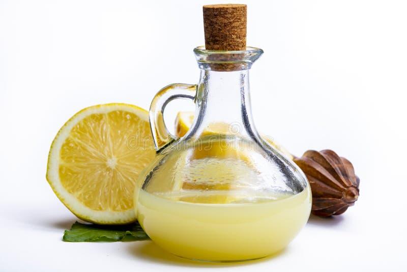 Jus de citron frais fait à partir des citrons siciliens jaunes mûrs utilisés pour faire cuire dans la bouteille en verre sur le p photo libre de droits