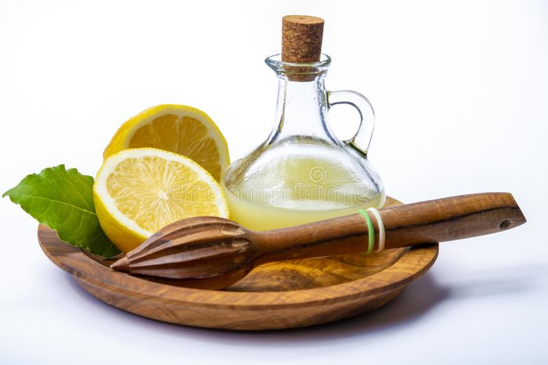 Jus de citron frais fait à partir des citrons siciliens jaunes mûrs utilisés pour faire cuire dans la bouteille en verre sur le p photos stock
