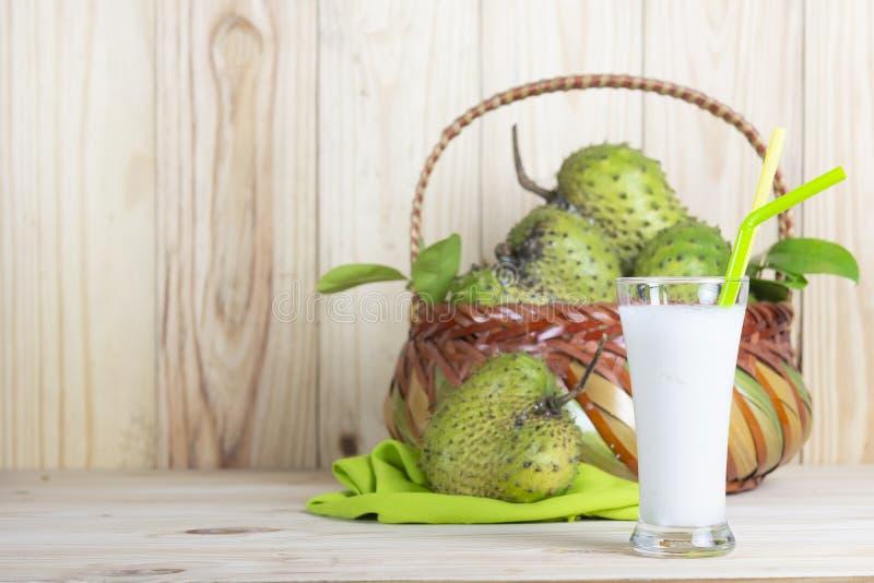 Jus de corossol hérisse avec le fruit de corossol hérisse dans le panier sur la table en bois photographie stock