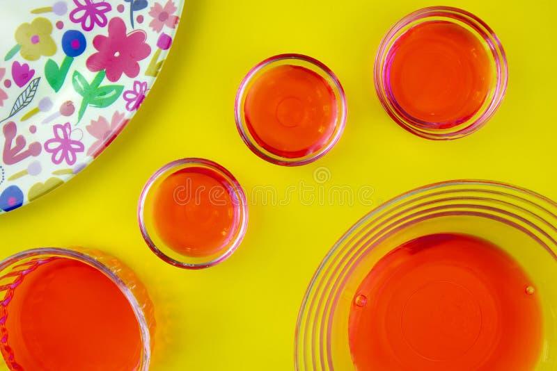 Jus de fruit rouge dans des bols en verre et le plat brillamment coloré sur le fond jaune photo libre de droits