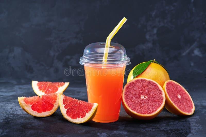 Jus de pamplemousse dans la tasse en plastique avec des fruits frais sur la table foncée photo libre de droits