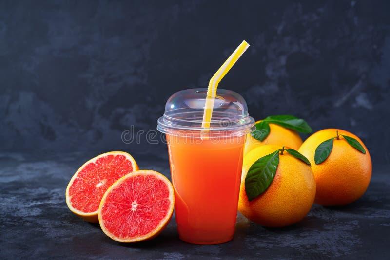 Jus de pamplemousse dans la tasse en plastique avec des fruits frais sur la table foncée photo stock
