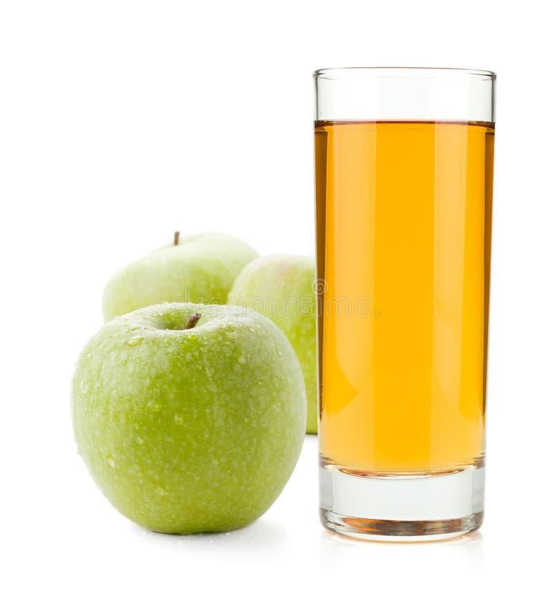 Jus de pomme dans les pommes en verre et vertes photographie stock libre de droits