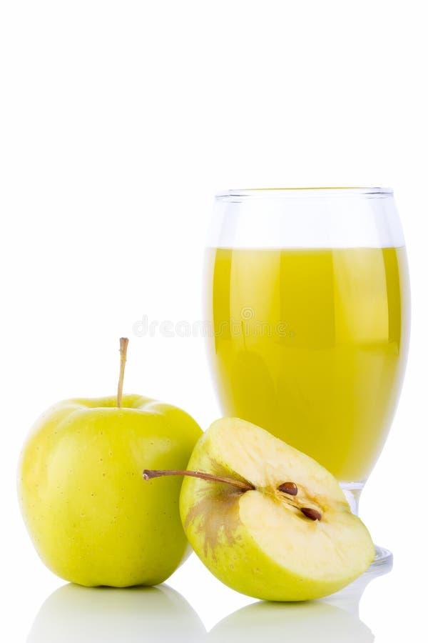 Jus de pomme dans les pommes en verre et vertes images stock
