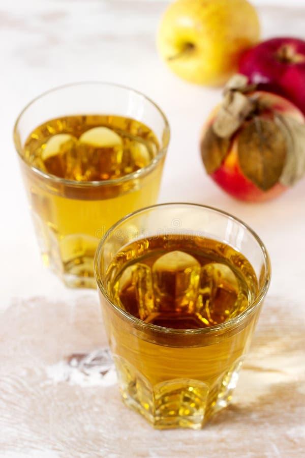 Jus de pomme dans les verres et les pommes fraîches sur un fond en bois Type rustique photos stock