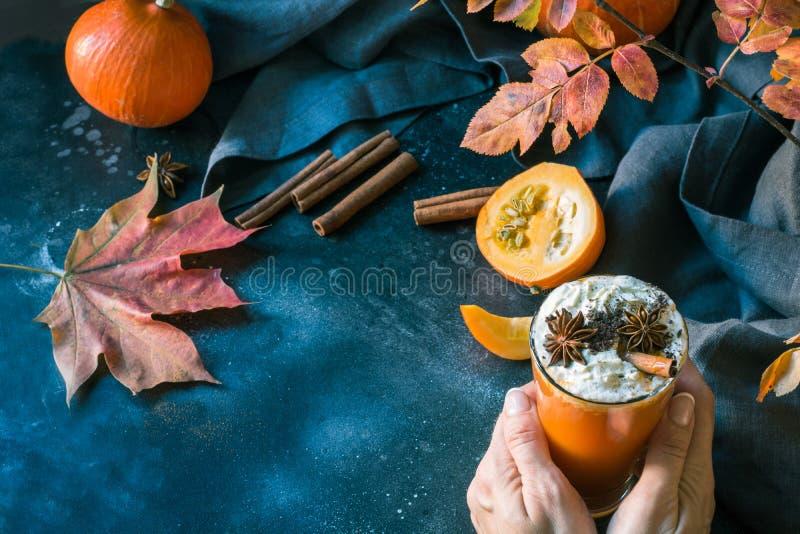 Jus de potiron avec la crème fouettée dans la main femelle sur l'obscurité Boisson chaude d'automne, de chute ou d'hiver Boisson  photo libre de droits