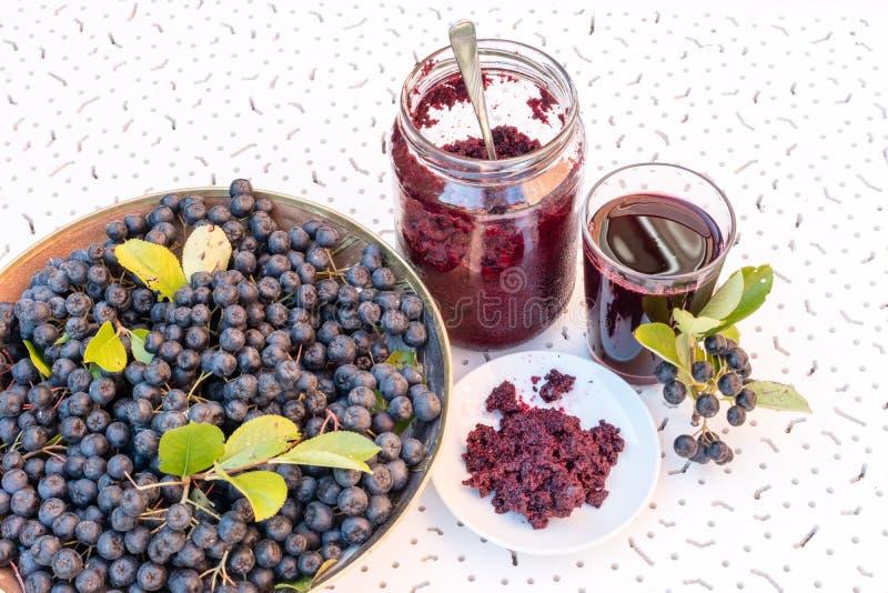 Jus et confiture frais de melanocarpa noir d'Aronia de chokeberry dans le verre et la baie dans le pot sur le fond texturisé blan photo stock