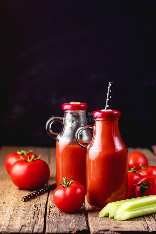 Jus frais de céleri de tomate dans une bouteille en verre sur une verticale saine savoureuse de boissons de Detox de fond en bois photo libre de droits
