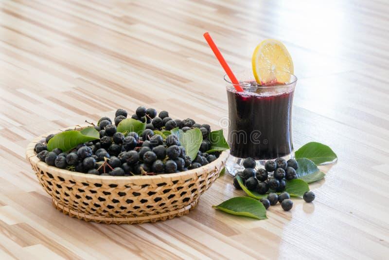 Jus frais de chokeberry ou de melanocarpa d'Aronia avec de la glace et le citron dans le verre et la baie dans le baske photographie stock