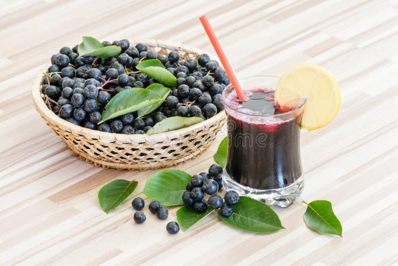 Jus frais de chokeberry ou de melanocarpa d'Aronia dans le verre et la baie dans le pot sur en bois image stock