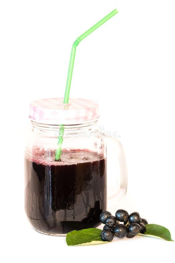 Jus frais de chokeberry ou melanocarpa d'Aronia en verre avec la paille et la baie et les feuilles près, d'isolement sur le fond  image libre de droits