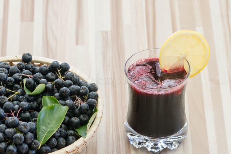 Jus frais de chokeberry ou de melanocarpa d'Aronia en verre avec la tranche de glace et de lemone, baie dans le panier photo libre de droits