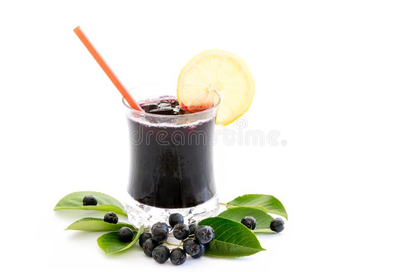 Jus frais de melanocarpa d'Aronia de chokeberry en verre et baie et feuilles près, d'isolement sur le blanc photo stock