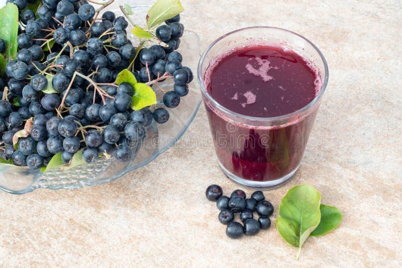 Jus frais de melanocarpa noir d'Aronia de chokeberry dans le verre et la baie dans le pot sur le fond en céramique brun images libres de droits