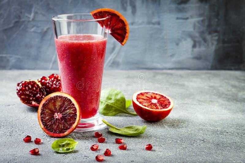 Jus ou smoothie frais de Detox en verre avec des oranges sanguines, verts, grenade Boisson régénératrice faite maison de fruit Co photo libre de droits