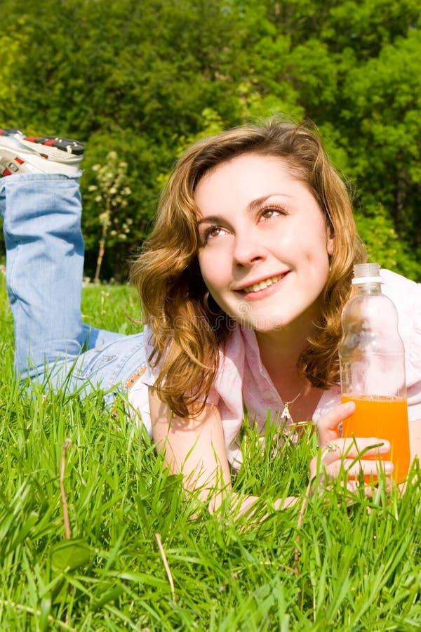 Jus potable de femme sur la clairière d'été image stock