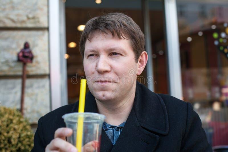 Jus potable de jeune homme en café de ville photos libres de droits