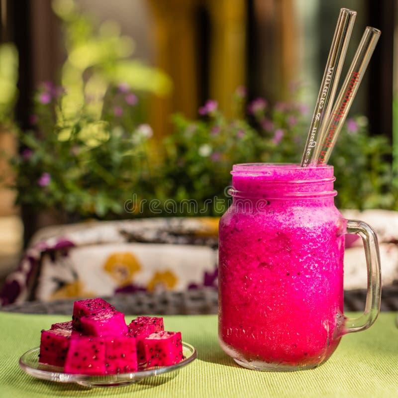 Jus rouge de fruit du dragon dans un verre avec deux pailles en verre, fruit du dragon coupé d'une glace Fleurs sur un fond image stock