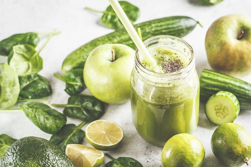 Jus sain vert de smoothie dans le pot Apple, épinards, smoothie de concombre sur le fond blanc avec les ingrédients photographie stock libre de droits