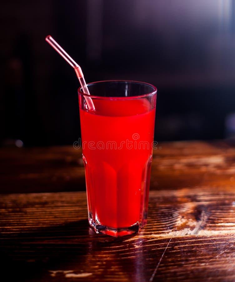 Juse rosso su uno scrittorio della tavola, fondo scuro immagine stock