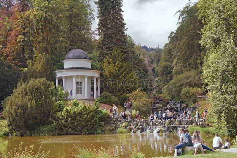 Jussowtempel 人步行在公园 水小瀑布在Wilhelmshoeh 图库摄影