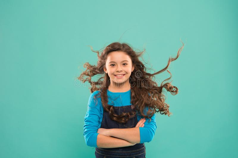 Just amazing. Happy child with long curly hair on blue background. Small child smiling with beauty look. Brunette female stock images