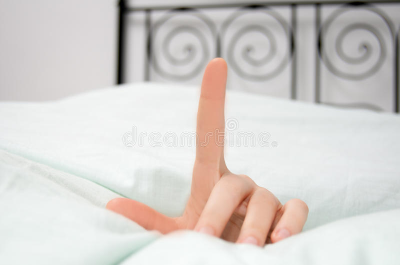 Just another minute. Hand sign in the morning in bed stock photo