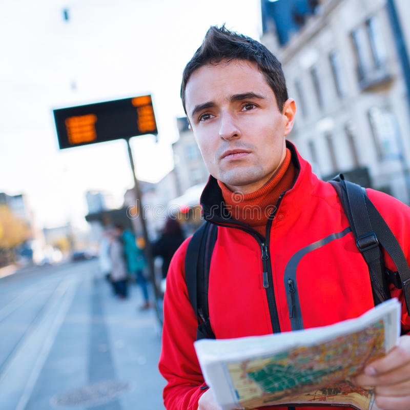Just arrived: handsome young man studying a map on a bus stop. In front of a train station royalty free stock images