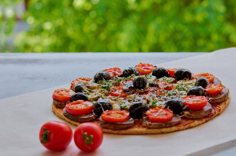 Just backed veggie pizza with mushrooms, black olives and herbs on the gray kitchen table decorated with fresh cherry tomatoes stock image