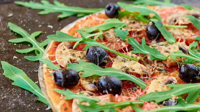 Just baked hot pizza on the black background close up. Vegetarian pizza with vegetables, black olives and fresh rucola royalty free stock image