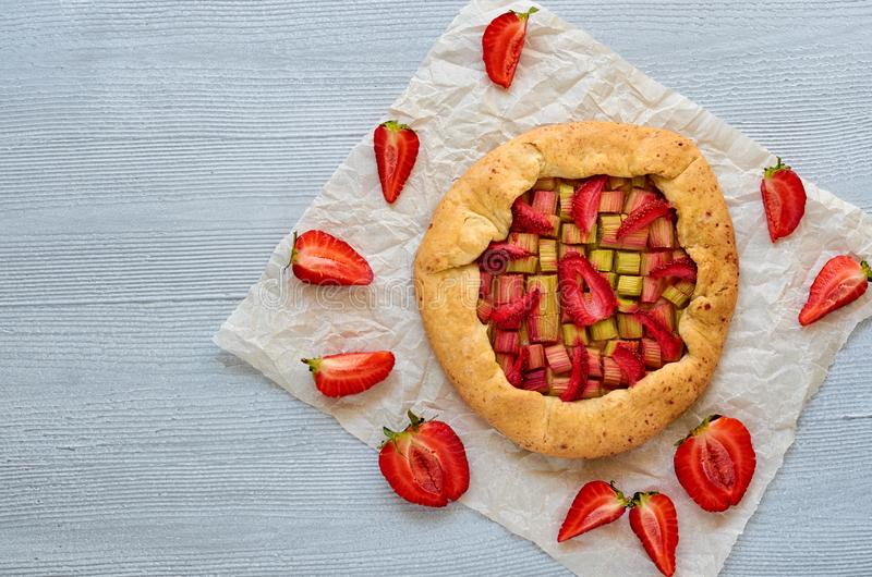 Just baked strawberry tart on the gray background with copy space. Vegetarian healthy rhubarb galette royalty free stock photo