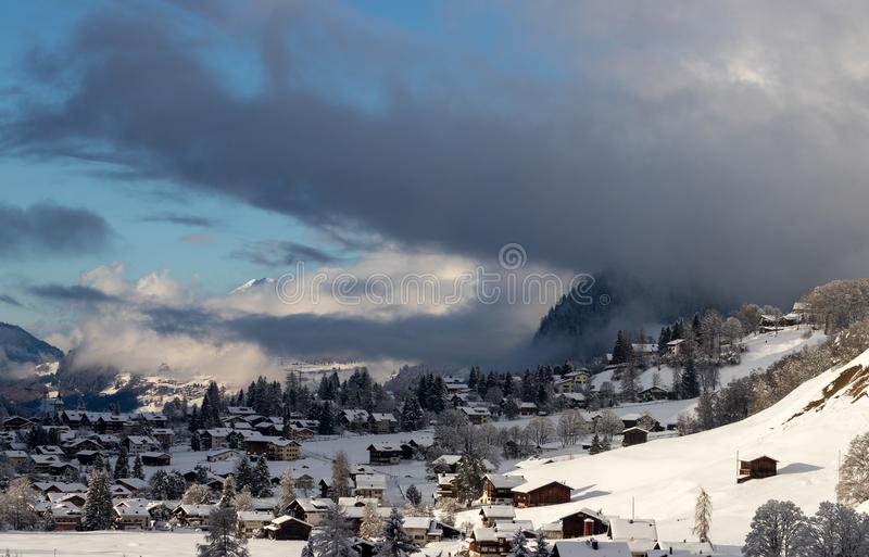 Just before blizzard. Clouds moving over the village of Klosters in Switzerland just before a snow storm stock image