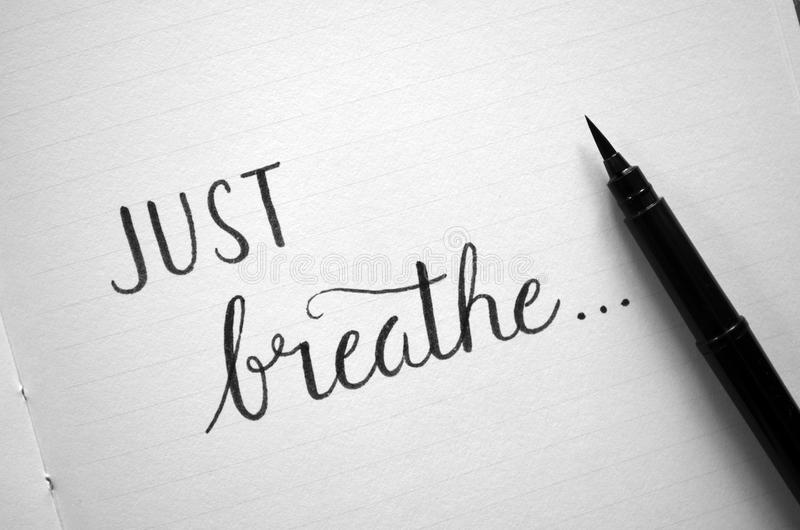 `JUST BREATHE` hand-lettered in notebook royalty free stock images
