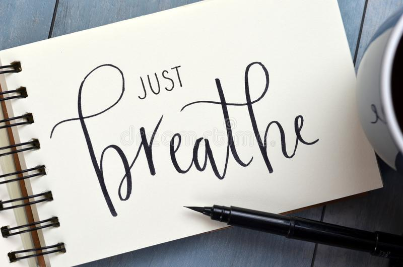 JUST BREATHE hand-lettered in notepad with brush pen royalty free stock image