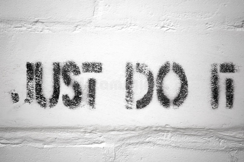 Just do it. Textured black stencil print of just do it phrase on the grunge brick wall stock photos