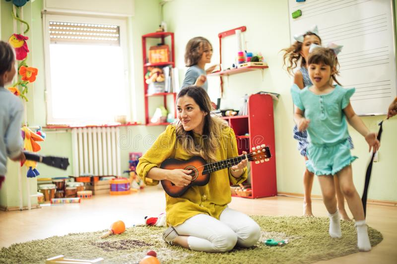 Just follow the music. Children with teacher in preschool royalty free stock photography