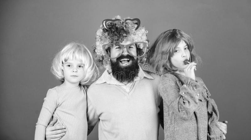 Just for fun. Party time. How crazy is your father. Man bearded father and kids girls wear colorful wig violet stock image