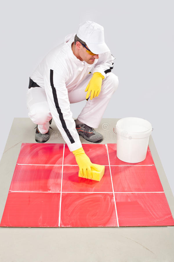 Just grouted tilles cleaning. Worker with yellow gloves and yellow sponge clean tiles joints from white grout material royalty free stock images