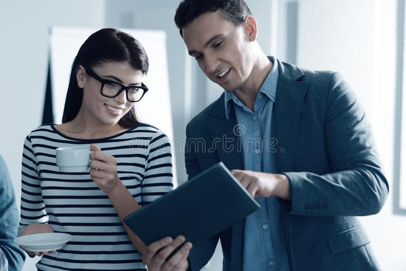 Young positive colleagues using tablet in the office royalty free stock image