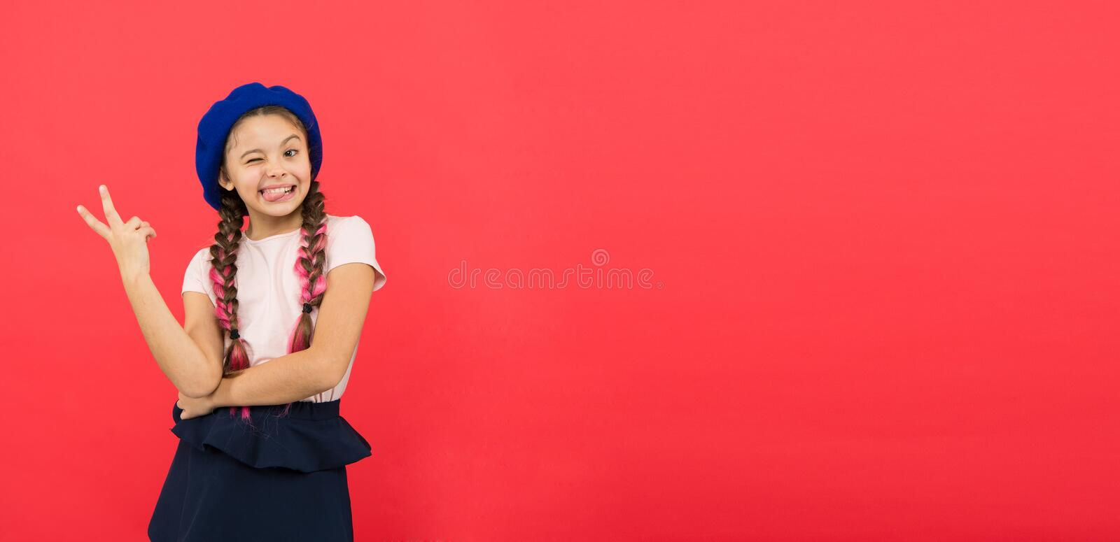 Just having fun. Summer holidays. Kid little cute fashion girl posing with long braids and hat red background. Child stock images